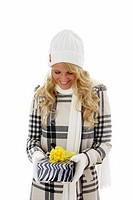 young blonde in gloves, head wear, winter coat and muffler holding a present