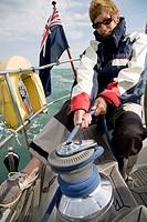 Woman hoisting sails on yacht