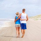 Rear view of couple walking on seashore