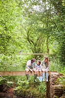 Family sitting talking on country bridge