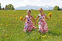 Two girls on dandelion meadow