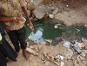 Kids playing with rubbish at a dirty sewer in a big slum, India