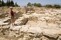 A tourist standing amid the excavation site of the Minoan palaces of Festos, island of Crete, Greece, Europe