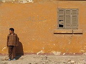 Young boy in front of outsid wall with arabic scripture _ inhabitant of the ´City of the living dead´ very large cemetery in Cairo, Egypt, Kairo, Kair...