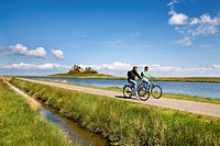 Cyclist in front of Kirchwarft dwelling mound, Hallig Hooge, North Frisia, Schleswig-Holstein, Germany, Europe