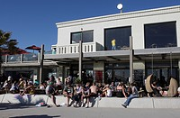 People sitting in and in front of a beach cafe in St. Kilda, a suburb of Melbourne, Victoria, Australia