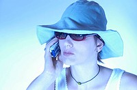 young woman with sun hat and sun glasses phoning with mobile, Germany