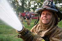 A female volunteer firefighter sprays water on a fire, Shipshewana, Indiana, USA