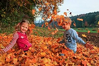 girl and boy playing in pile of leaves, fall Zuerich, Switzerland