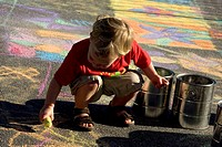 toddler plays with chalk at sidewalk arts festival