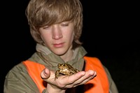 European common toad Bufo bufo, young conservationist with toad on his hand, Germany, Baden_Wuerttemberg