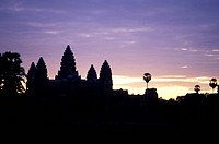 Towers of Angkor Wat and palm trees silhouetted at sunset