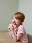 7_8 year old girl smiles as she eats a piece of melon