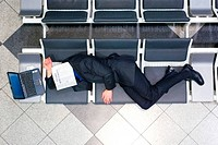 young businessman with a laptop in the waiting area of an airport, lying on a bench