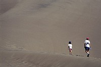 Great Sand Dunes National Monument, Colorado - A mother and her daughter climb a sand dune  The dunes cover 30 square miles and rise more than 750 fee...