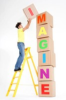 Man stacking boxes to spell imagine (thumbnail)