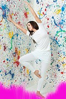 Woman with arms raised and walls covered in paint