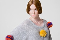 Woman wearing a sweater with pom poms