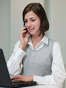 Businesswoman with laptop and cellphone