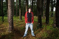 Young man standing in forest (thumbnail)
