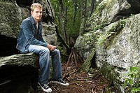 Teenage boy sitting on rock