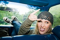 Young woman in car making hand gesture