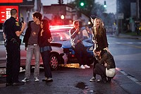 Young people and police officer at scene of car crash (thumbnail)