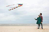 Young couple with kite by the sea