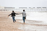 Couple running hand in hand by the sea