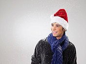 Young man wearing santa hat in snow