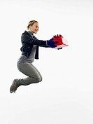 Young woman jumping with christmas gift