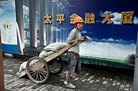 a worker carries goods in a wheelbarrow. Shanghai, China