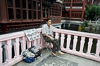 a man selling pictures in a tourist attraction. Shanghai, China