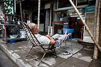 A man sleeping outside the door of his business. Shanghai, China