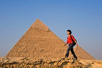 Woman with rucksack walking along ancient wall in front of Pyramids