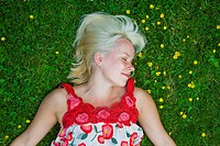A laughing blonde woman in a park.