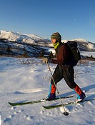 Young woman backcountry skiing, alpine tundra, Fish Lake behind, Yukon, Canada, North America