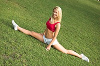 A pretty young blonde woman doing the splits