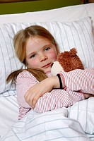 Girl, 7 years, with teddy in bed