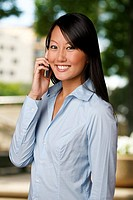 An Asian woman speaks with a friend on her cell phone