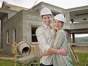 Couple hugging outside house under construction