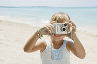 Girl with digital camera on beach