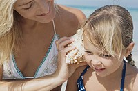 Mother holding shell up to daughter's ear on beach