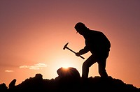 Silhouette of man hitting pile of rocks with hammer while yellow sunset in the background