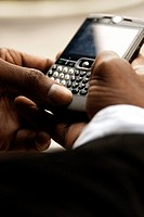Close up of African man text messaging on cell phone