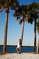 Alluring, sexy woman in feminine dress, standing near ocean leaning on palm trees