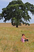 Woman sits in grass field by large oak tree, Oakdale, California, USA