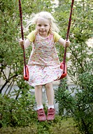Girl wearing a dress, on a swing in Landshut, Bavaria, Germany, Europe