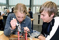A BMW AG trainee teaching a girl student how to solder in the apprenticeship workshop during the Girl's Day on April 27, 2006 at the BMW plant in Rege...