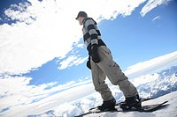 Wintersport snowboard man looking out over the top of the winter mountains of the Austrian Alps, Tyrol, Tirol, Austria